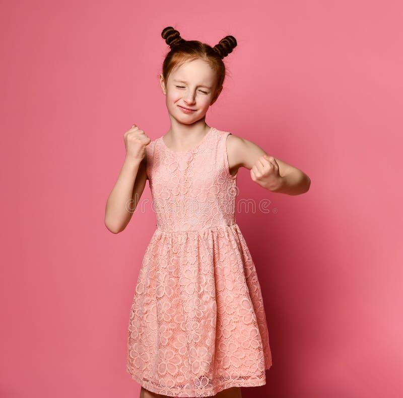 La muchacha pelirroja seria defiende sus puños con encajonado Expresión del concepto de las emociones y de las sensaciones imagenes de archivo