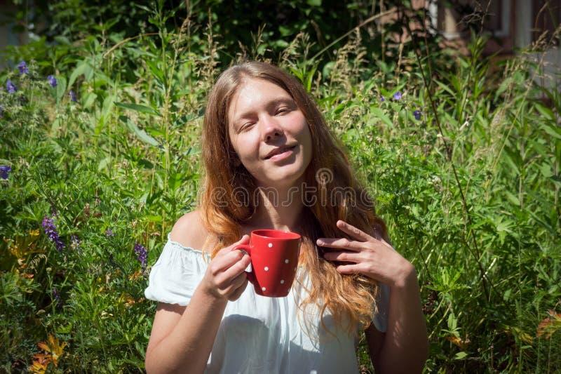 La muchacha pelirroja sostiene en su mano una taza roja con té en el fondo de la hierba verde en el verano imagen de archivo libre de regalías