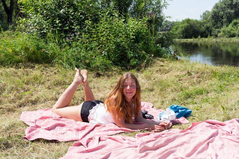 La muchacha pelirroja toma el sol en una colcha rosada en el riverbank en un día de verano soleado imagen de archivo