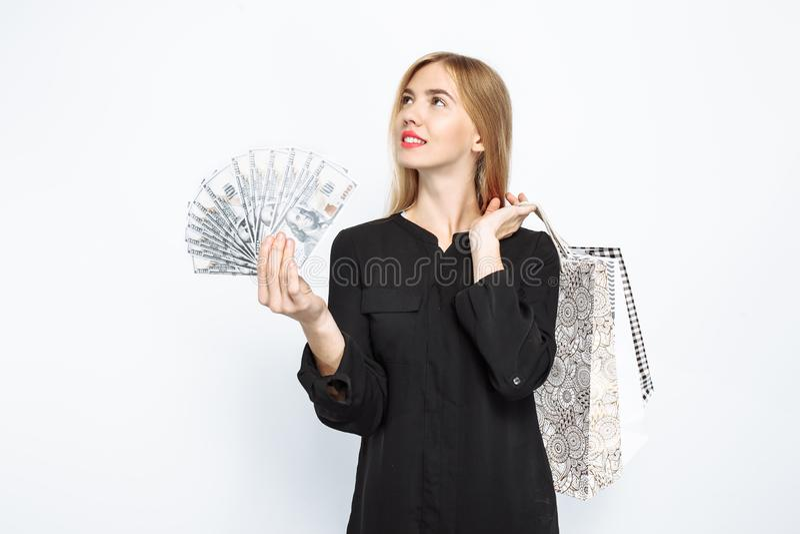 La muchacha pensativa en vestido negro y con los labios rojos sostiene bolsos, para sh foto de archivo