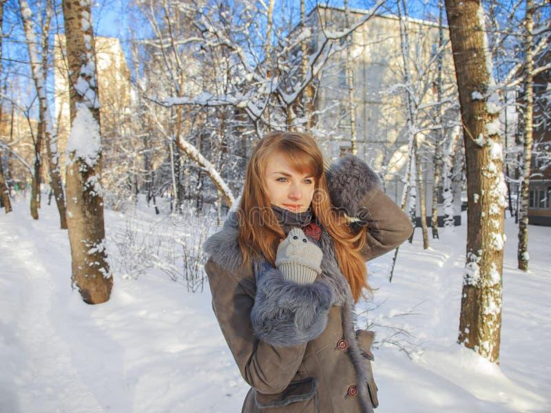 La muchacha pensativa hermosa con el pelo rojo está en el fondo de una ciudad del invierno en un día soleado fotos de archivo