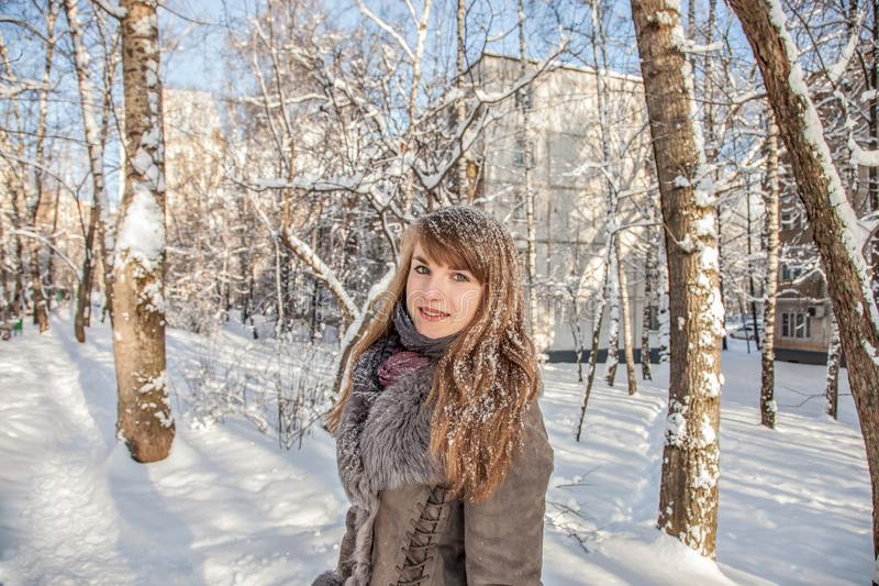 La muchacha pensativa hermosa con el pelo y los copos de nieve rojos en el pelo está en el fondo de una ciudad del invierno en un imagen de archivo