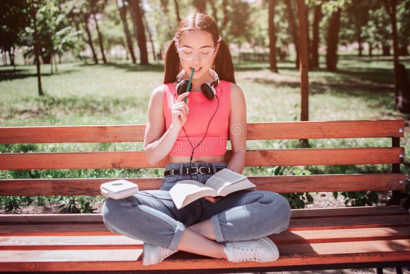 La muchacha pequeña y apuesta se está sentando en banco y está leyendo un libro Ella ha cruzado sus piernas y la masticación de u imagen de archivo