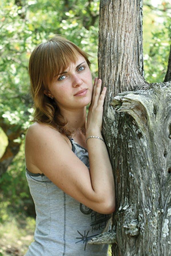 La muchacha permanece cerca del árbol foto de archivo libre de regalías