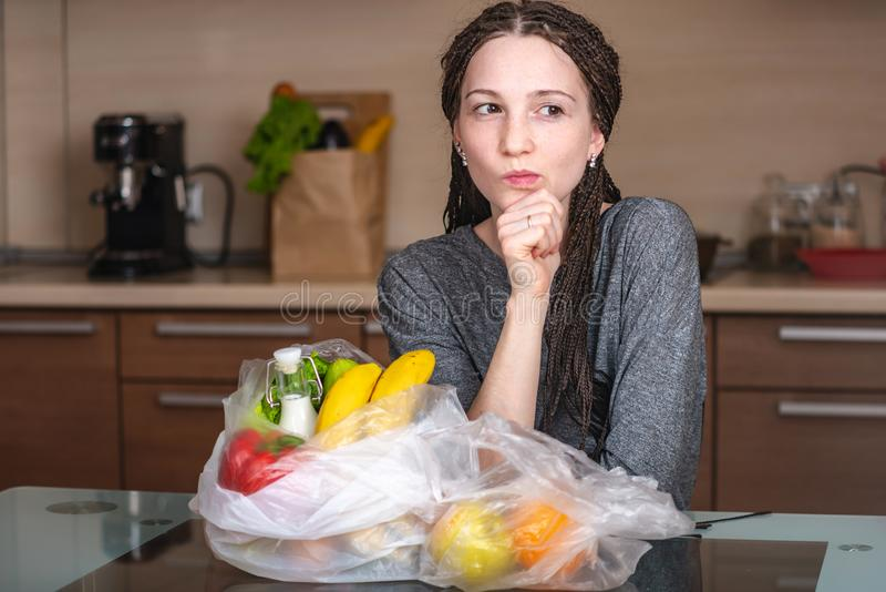 La muchacha piensa eso para rechazar utilizar una bolsa de plástico para comprar productos Protección del medio ambiente y el a fotografía de archivo