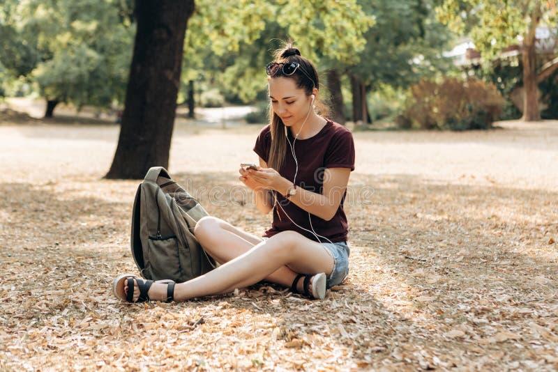 La muchacha positiva hermosa joven es que se sienta y que escucha la música imágenes de archivo libres de regalías