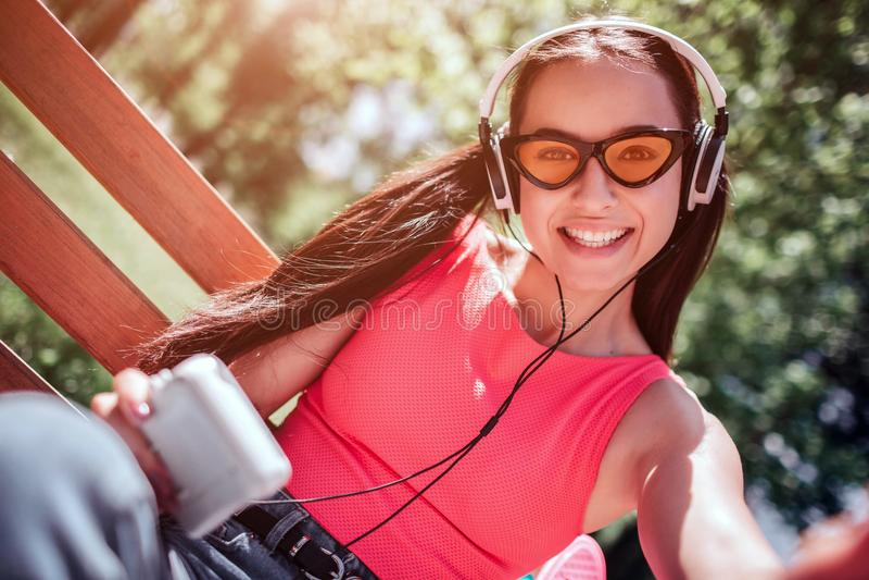 La muchacha positiva y feliz en vidrios extraños está tomando el selfie Ella está sonriendo a la cámara La muchacha está escuchan foto de archivo