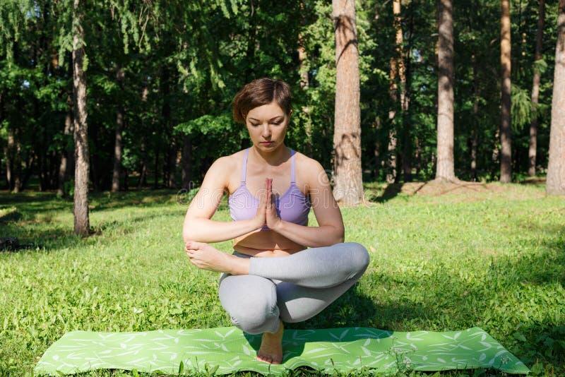 La muchacha practica yoga en el parque en un día soleado fotos de archivo