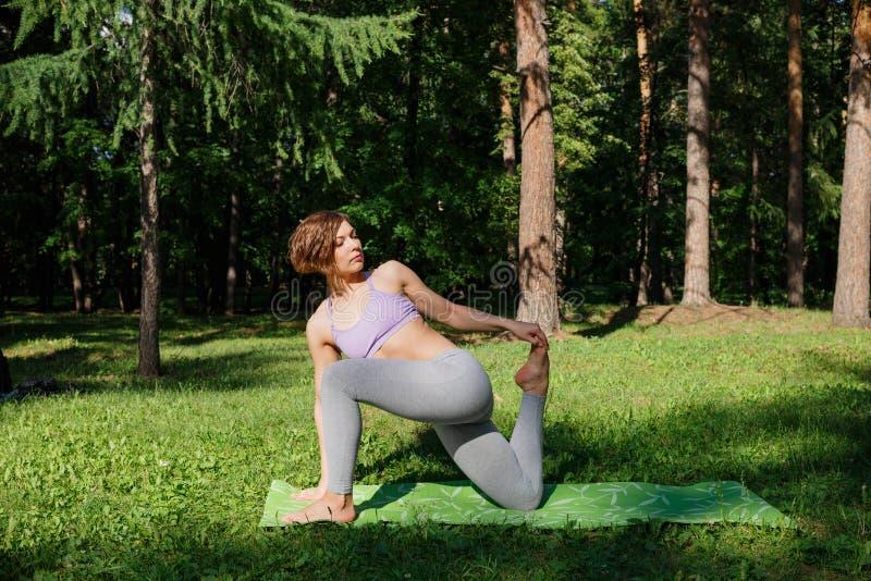 La muchacha practica yoga en el parque en un día soleado imagen de archivo