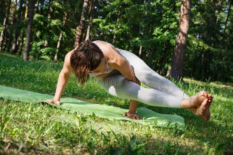 La muchacha practica yoga en el parque en un día soleado foto de archivo libre de regalías