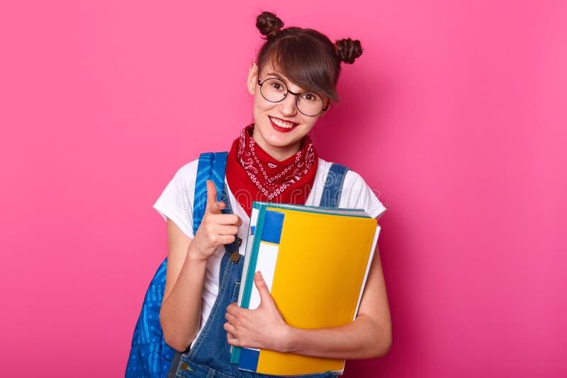 La muchacha preciosa joven celebra carpetas de papel coloreadas multi a disposición y la sonrisa, aislada en fondo rosado del bri foto de archivo