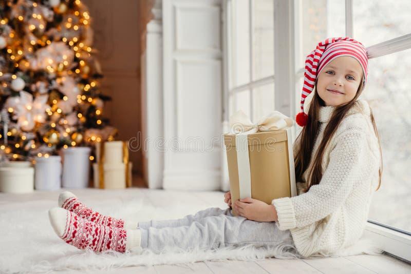 La muchacha preciosa linda con el presente, se sienta cerca de ventana en sala de estar, fotografía de archivo