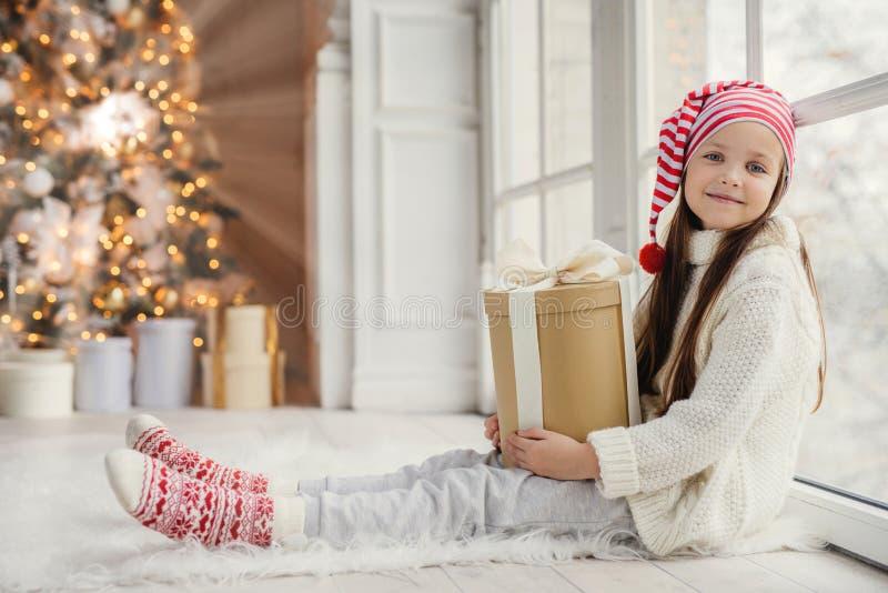 La muchacha preciosa linda con el presente, se sienta cerca de ventana en sala de estar, mira deliciosamente en cámara, admira de fotos de archivo