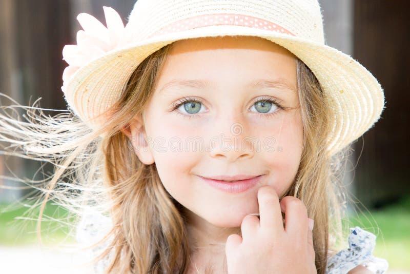 La muchacha preescolar encantadora con los ojos azules grandes y suelta de largo el sombrero de paja del pelo que lleva rubio que imágenes de archivo libres de regalías