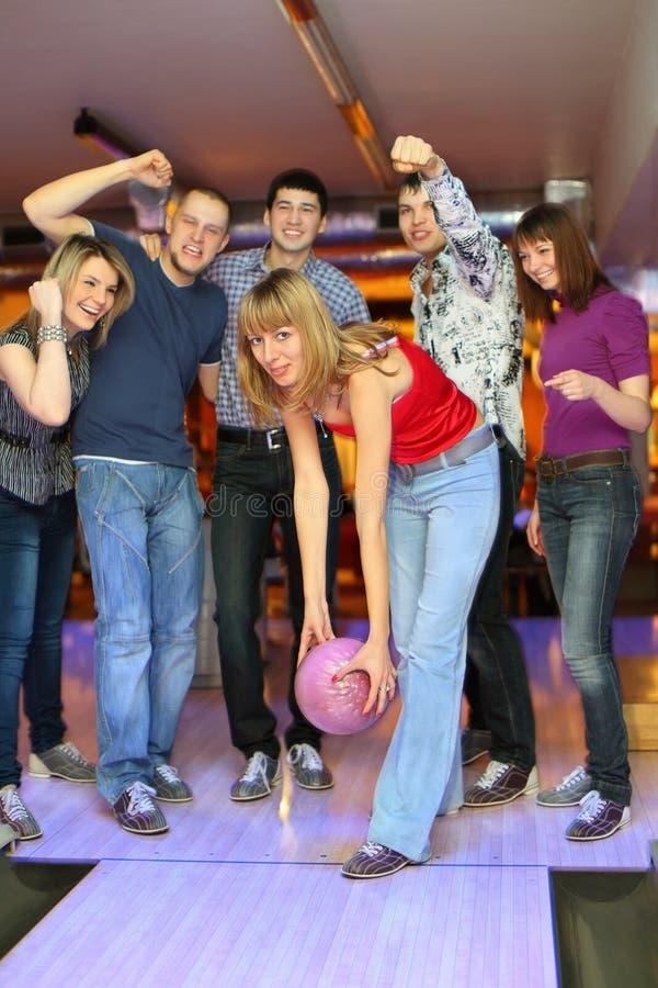 La muchacha prepara la bola del tiro en club del bowling imagen de archivo