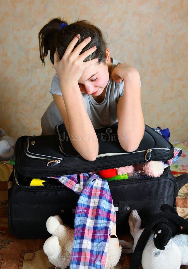 La muchacha puso la ropa en el caso cansado fotos de archivo libres de regalías