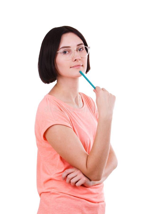 La muchacha puso un lápiz a su barbilla contra un fondo aislado blanco foto de archivo libre de regalías
