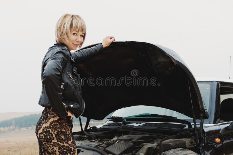 La muchacha que abre la capilla de su coche comprueba el nivel de aceite de motor imagen de archivo libre de regalías