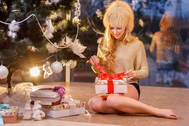 La muchacha que abre los regalos fotografía de archivo libre de regalías