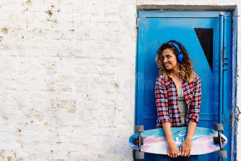 La muchacha que anda en monopatín sonriente que se coloca en la calle que lleva a cabo al largo-tablero anda en monopatín imagenes de archivo