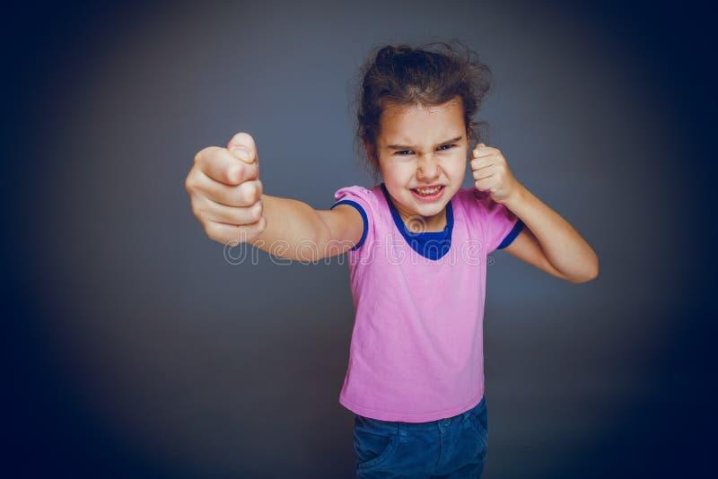 La muchacha que consigue el puño enojado muestra en un fondo gris foto de archivo libre de regalías
