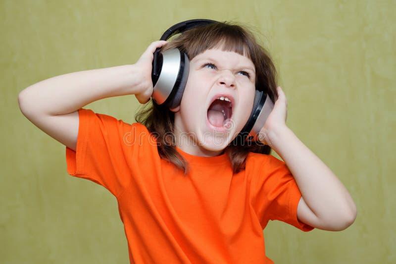 La muchacha que escucha la música en los auriculares y canta foto de archivo libre de regalías