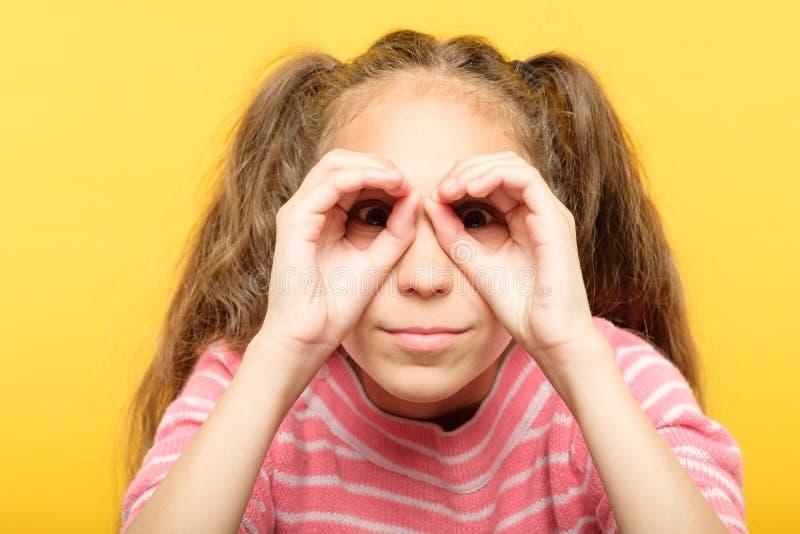 La muchacha que finge las manos de los prismáticos de la mirada busca imagenes de archivo