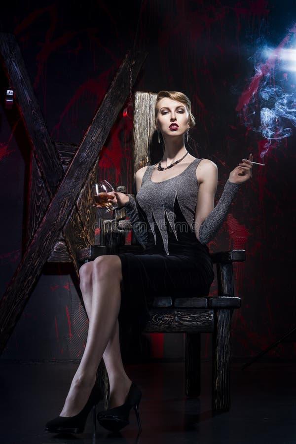 La muchacha que fuma con una copa en un interior del bdsm fotos de archivo libres de regalías