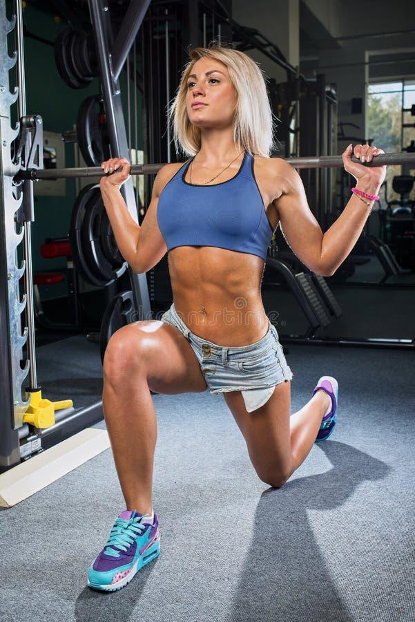 La muchacha que hace estocadas con la máquina del forjador en el gimnasio en un dril de algodón pone en cortocircuito y top del a fotografía de archivo libre de regalías