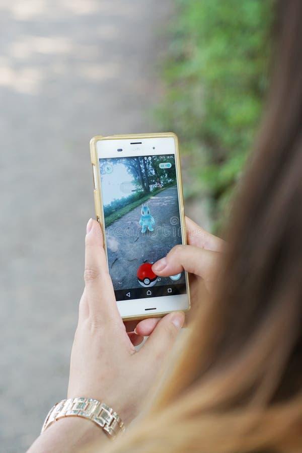 La muchacha que juega Pokemon va en su smartphone foto de archivo libre de regalías