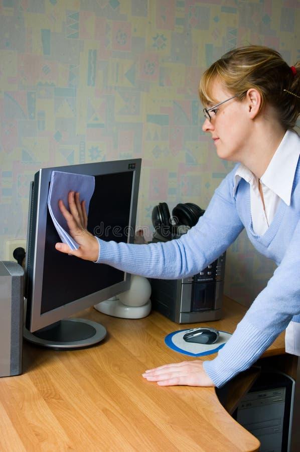 La muchacha que limpia el monitor fotografía de archivo