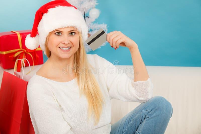 La muchacha que lleva el sombrero de Papá Noel sostiene la tarjeta de crédito para comprar fotos de archivo libres de regalías