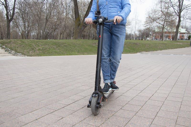 La muchacha que monta una vespa eléctrica en el parque con una cámara de la acción Transporte respetuoso del medio ambiente tecno foto de archivo
