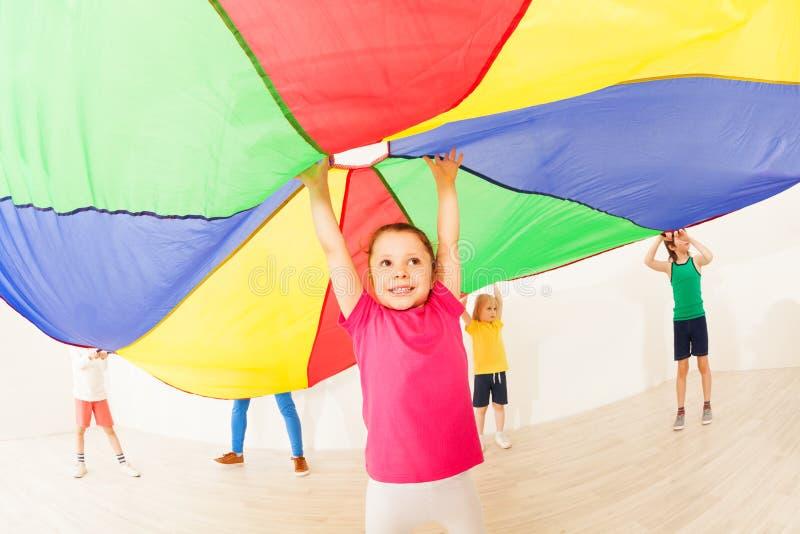 La muchacha que salta debajo de la tienda durante juegos del paracaídas imagen de archivo libre de regalías