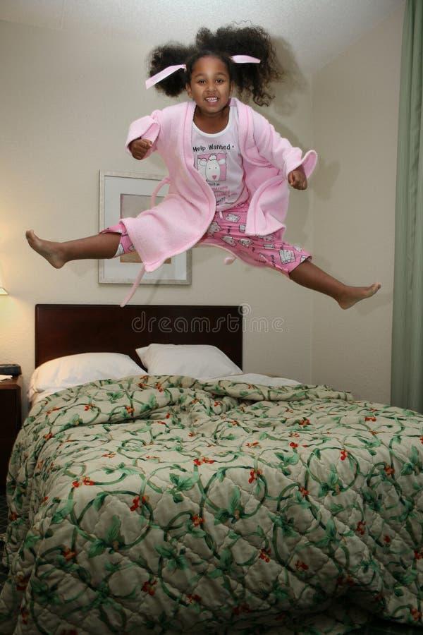 La muchacha que salta en cama imagen de archivo