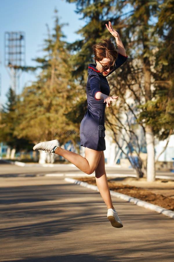 La muchacha que salta en el camino en parque foto de archivo