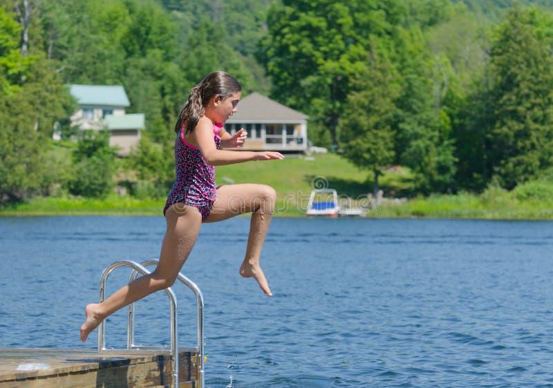 La muchacha que salta en el lago de muelle en la cabaña fotografía de archivo