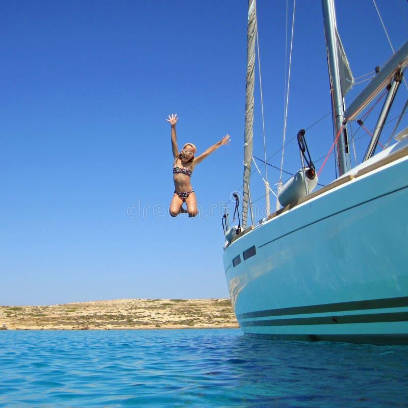 La muchacha que salta en el mar del barco imagen de archivo