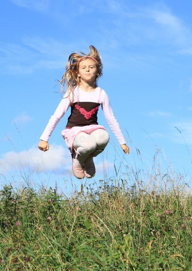 La muchacha que salta en hierba imagenes de archivo