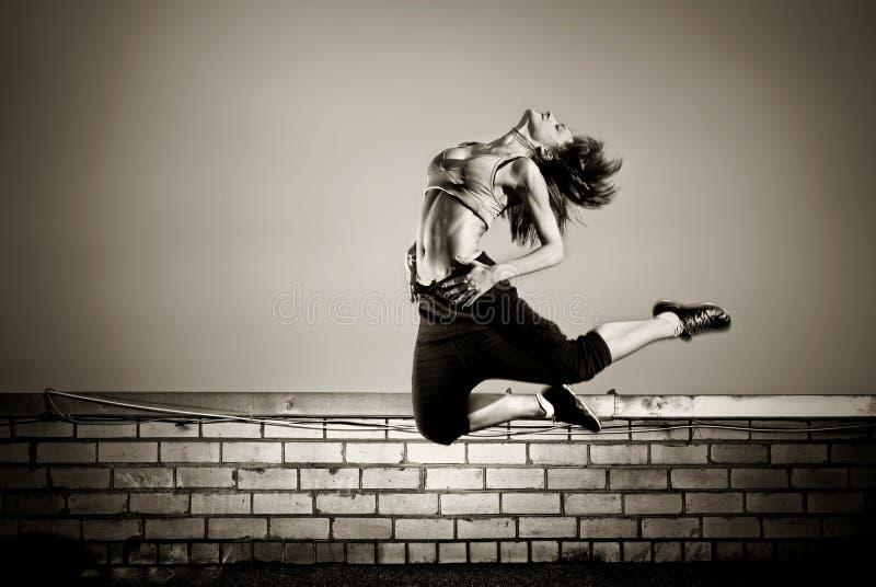 La muchacha que salta en la azotea imagen de archivo libre de regalías