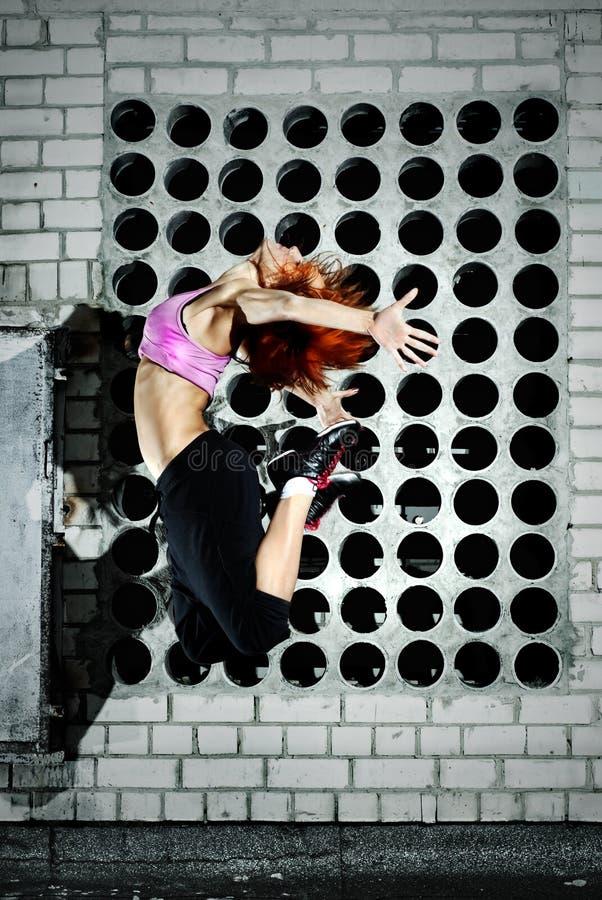 La muchacha que salta en la azotea foto de archivo libre de regalías