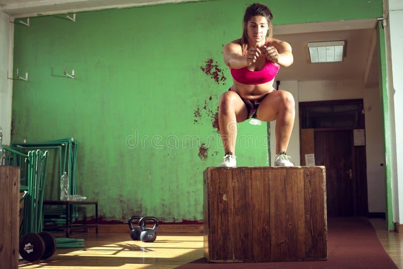 La muchacha que salta en la caja en gimnasio foto de archivo