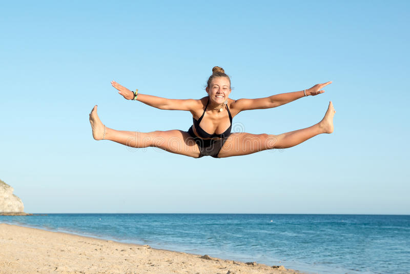 La muchacha que salta en la playa imagen de archivo libre de regalías