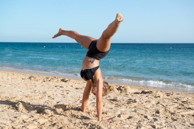 La muchacha que salta en la playa imagen de archivo