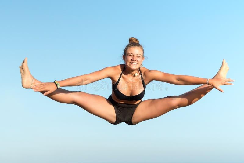 La muchacha que salta en la playa foto de archivo libre de regalías