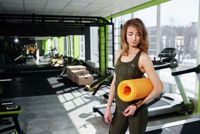 La muchacha que se coloca en el gimnasio sostiene una estera fotos de archivo