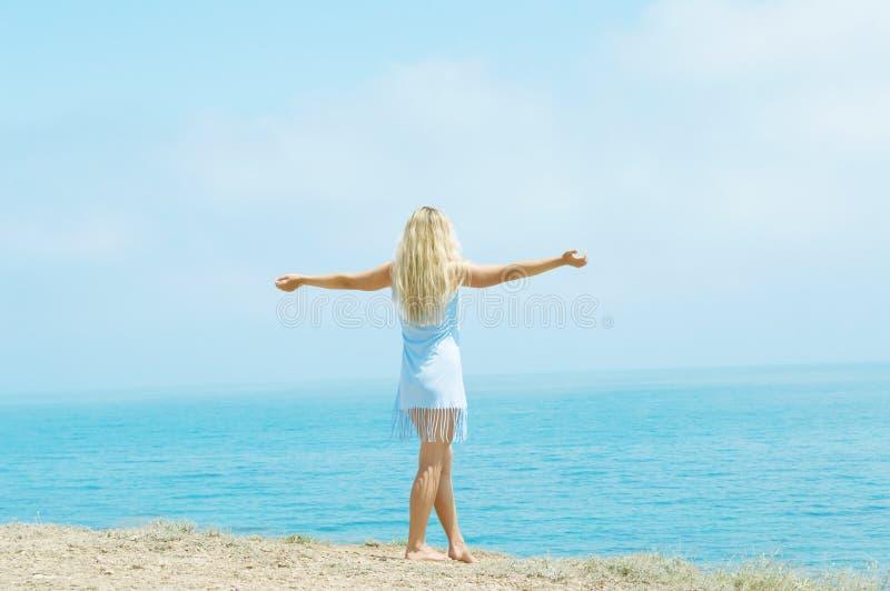 La muchacha que se coloca en la playa arma extendido imagen de archivo