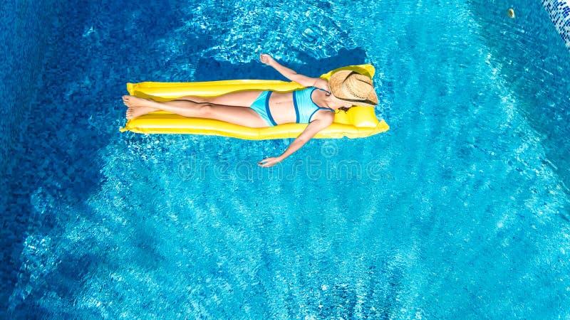 La muchacha que se relaja en piscina, niño nada en el colchón inflable y se divierte en agua el las vacaciones de familia, día de foto de archivo