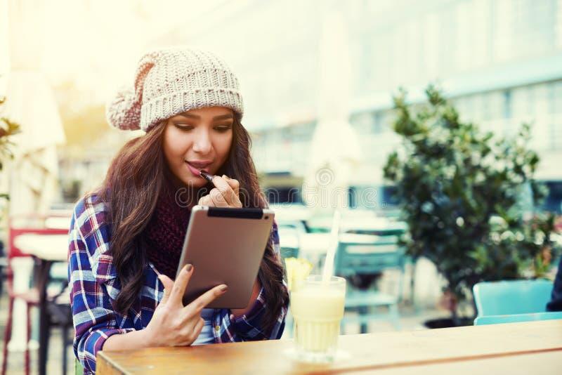 La muchacha que se sienta en un café en el aire abierto y ajusta su maquillaje fotografía de archivo