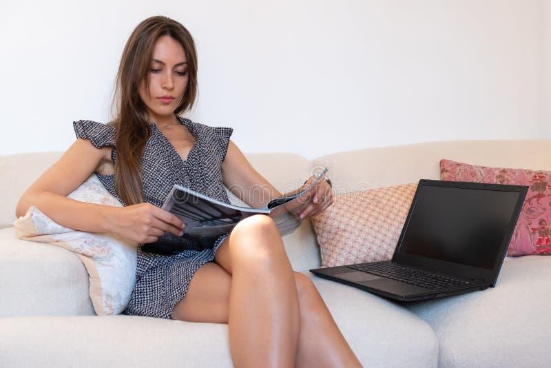 La muchacha que se sienta en un sofá lee una revista imágenes de archivo libres de regalías